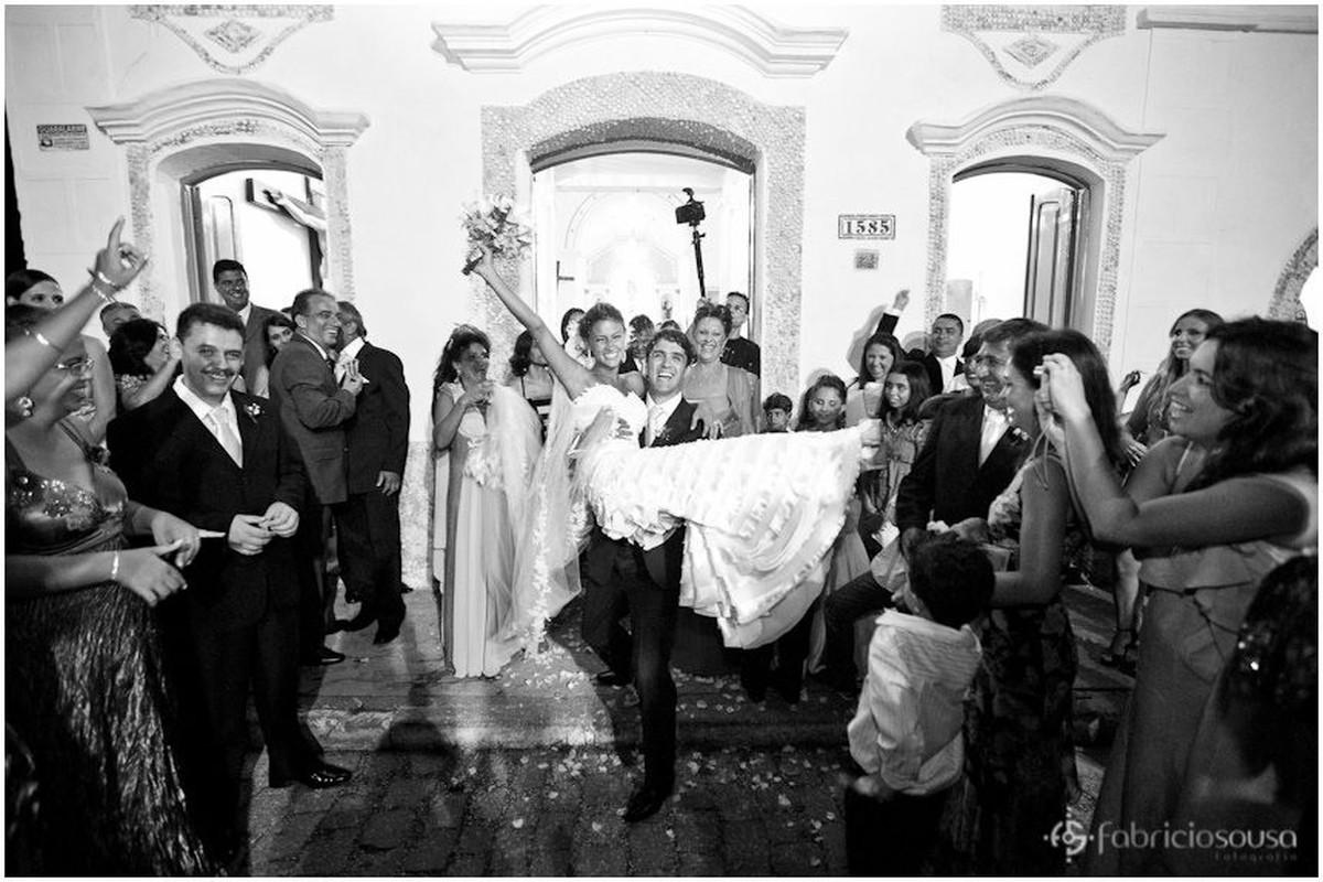 noivo carrega a noiva na saída