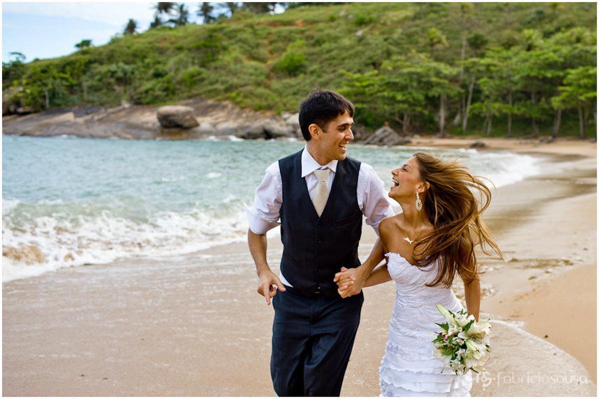 noivos correndo alegres na praia