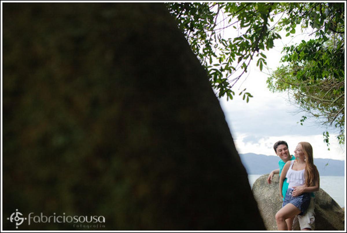 Fernanda e Luciano abraçados entre grandes pedras na beira do mar