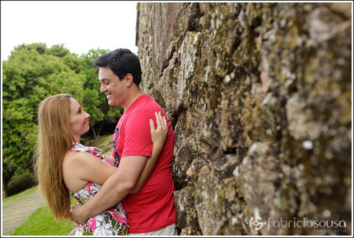 Namorada abraça o namorado escorado em muro de pedra