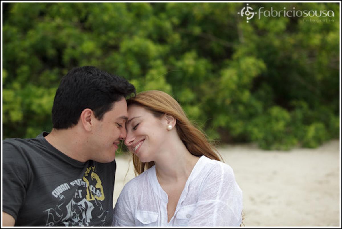 Casal de namorados sorrindo com rosto colado na areia da praia