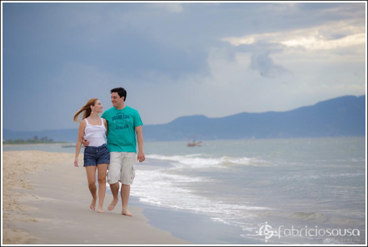 Casal de namorados caminham na beira do mar na praia
