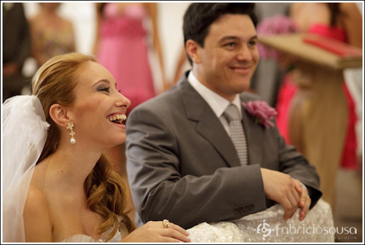 noivos sorrindo ajoelhados no altar