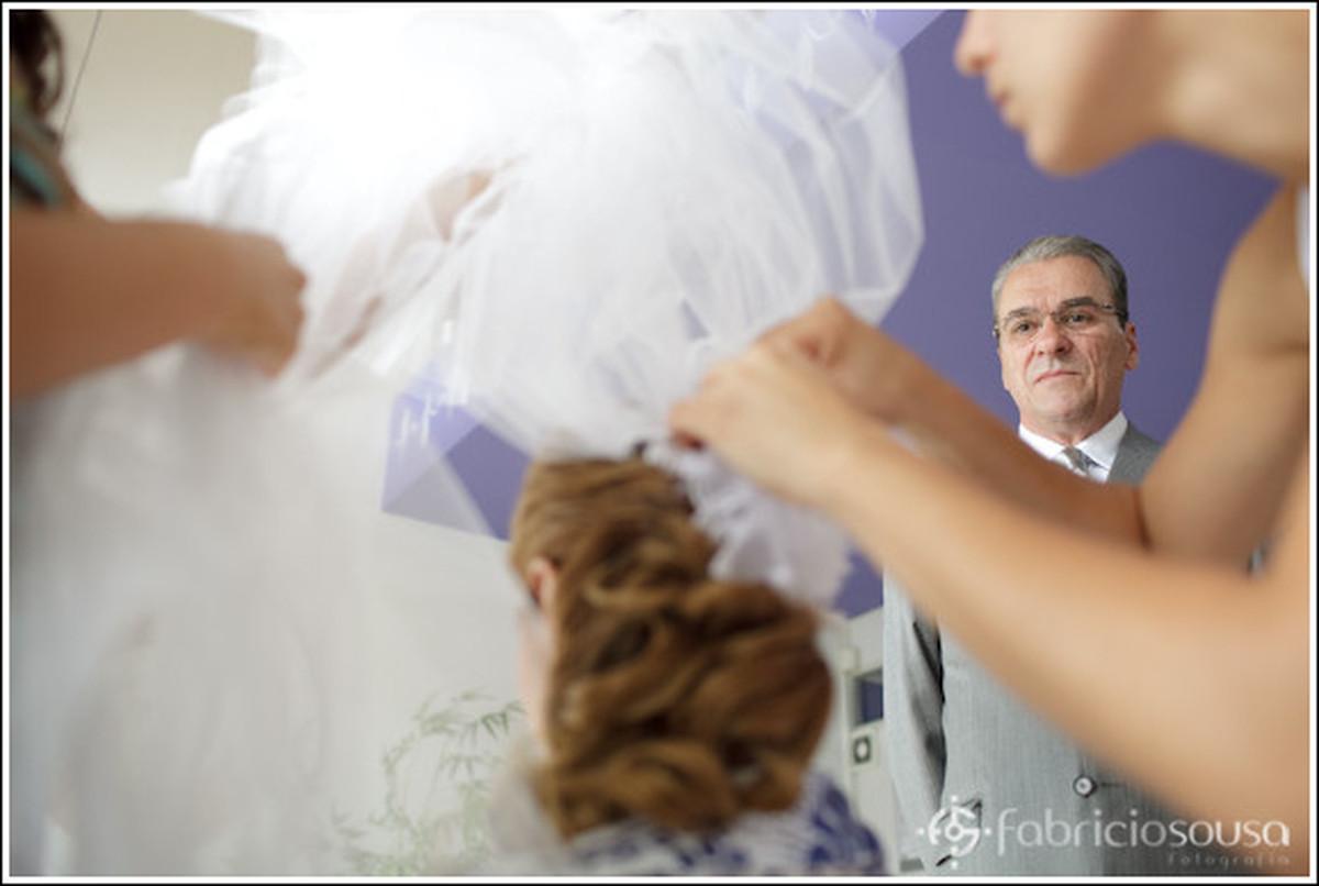 colocando o véu da noiva com o pai assistindo