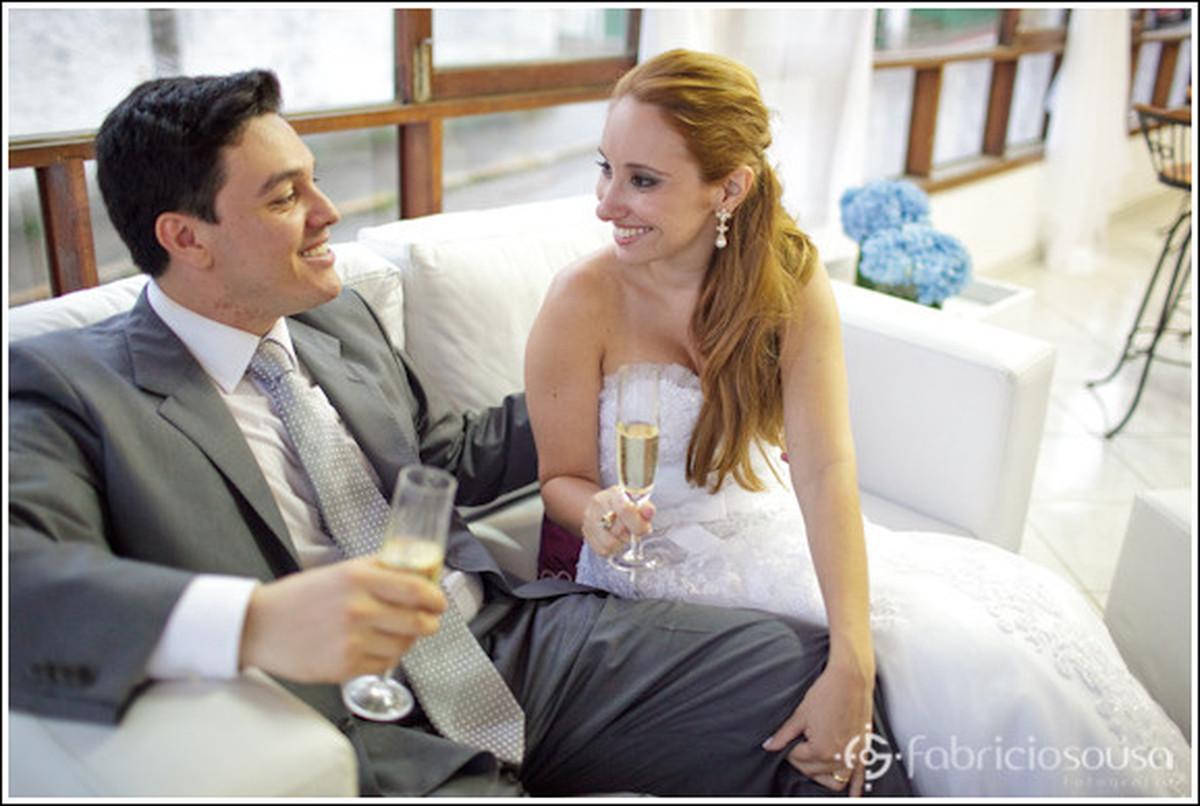 noivos tomando espumante no sofá em sua festa