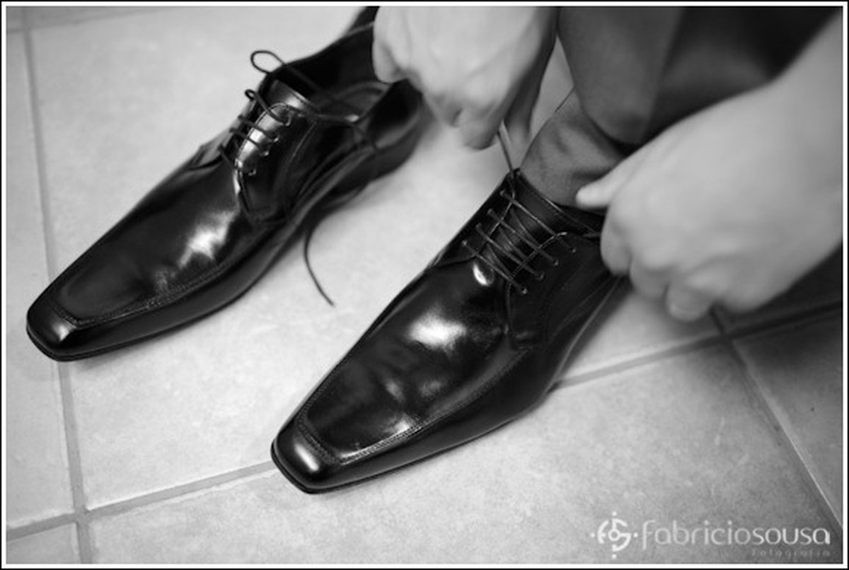 noivo colocando os sapatos no hotel