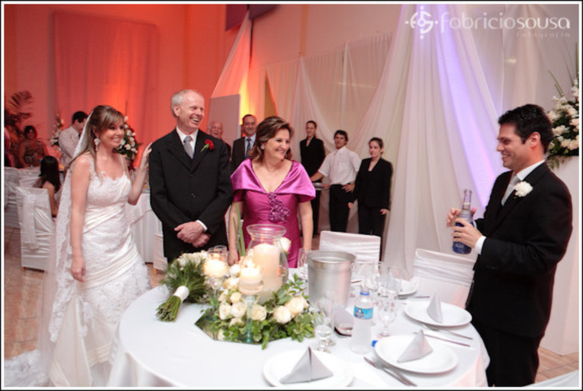 Casal de noivos em torno da mesa e de familiares