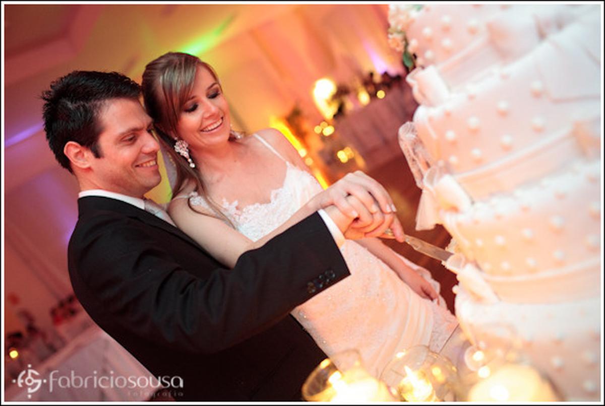 Recém casados cortam juntos o bolo