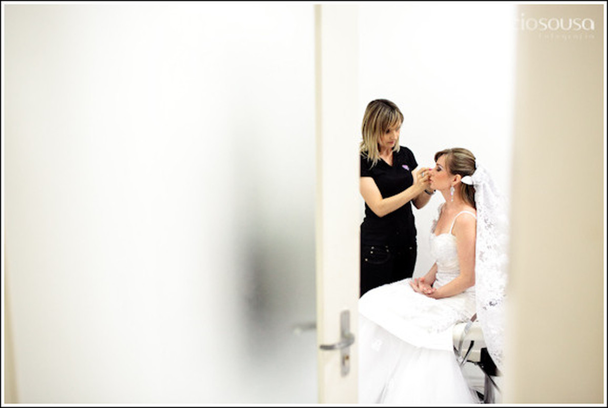 Maquiadora trabalhando com a noiva sentada