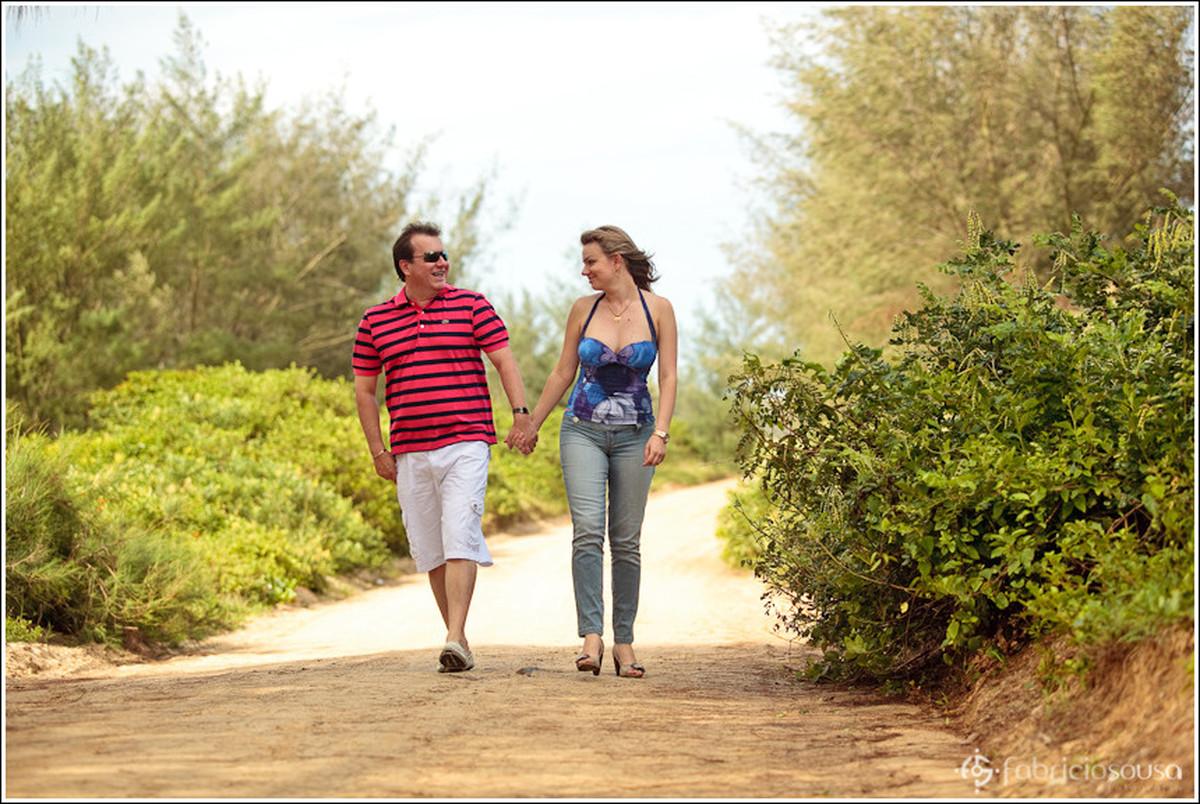 Namorado e namorada caminham de mãos dadas em estrada de terra