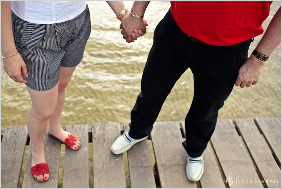 Detalhe das pernas de casal de namorados sobre pier na água