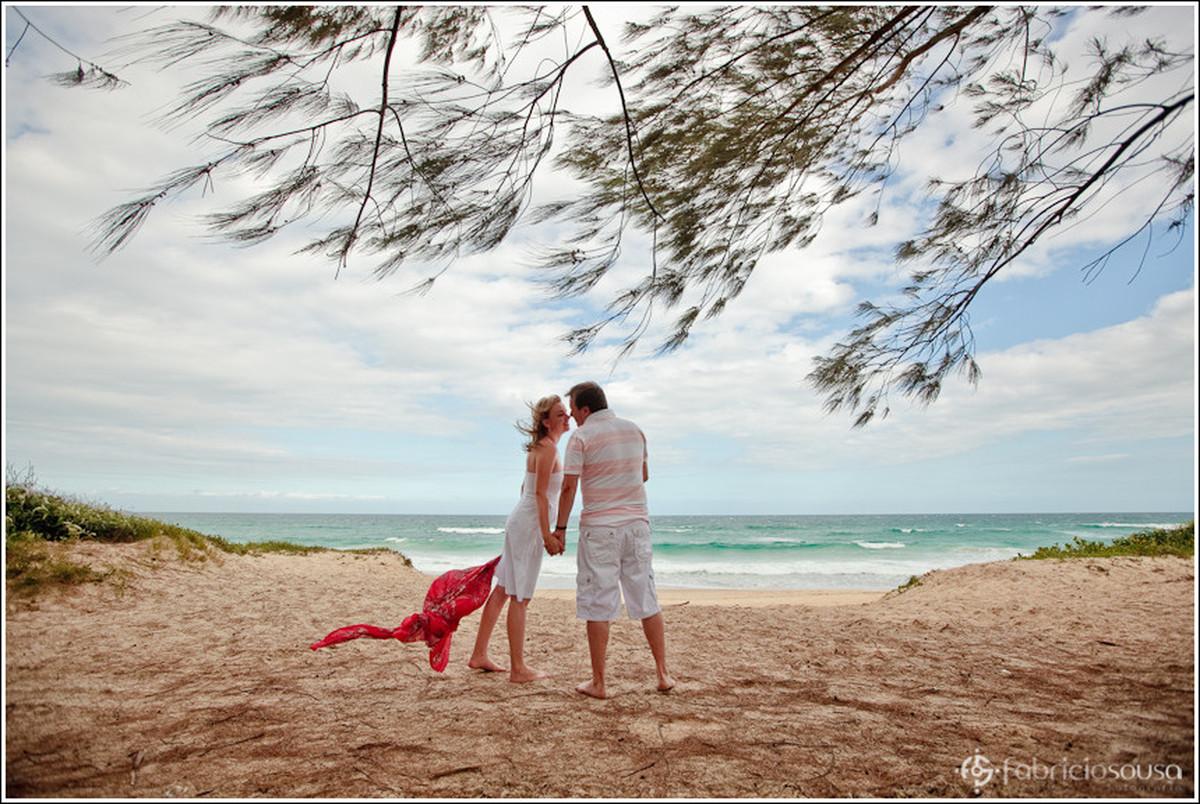 Namorados se beijam na praia de frente para o mar