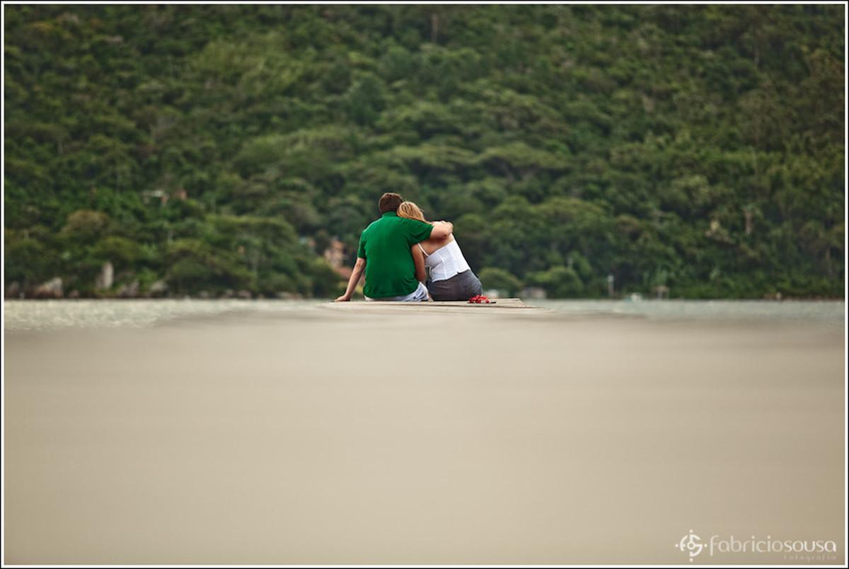 Ricardo abraça Leila sentados na areia da praia apreciando as belezas naturais em ensaio pre-wedding