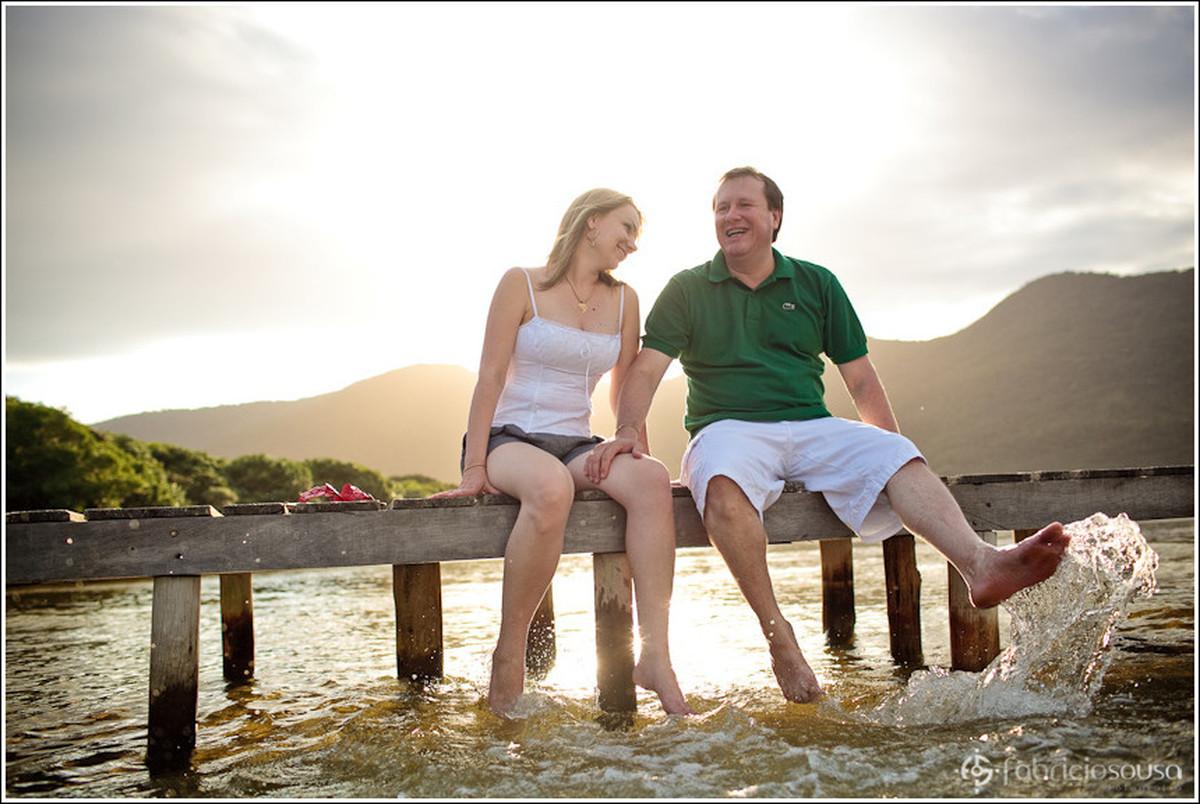 Futuros noivos brincam com os pés na água sentados no pier