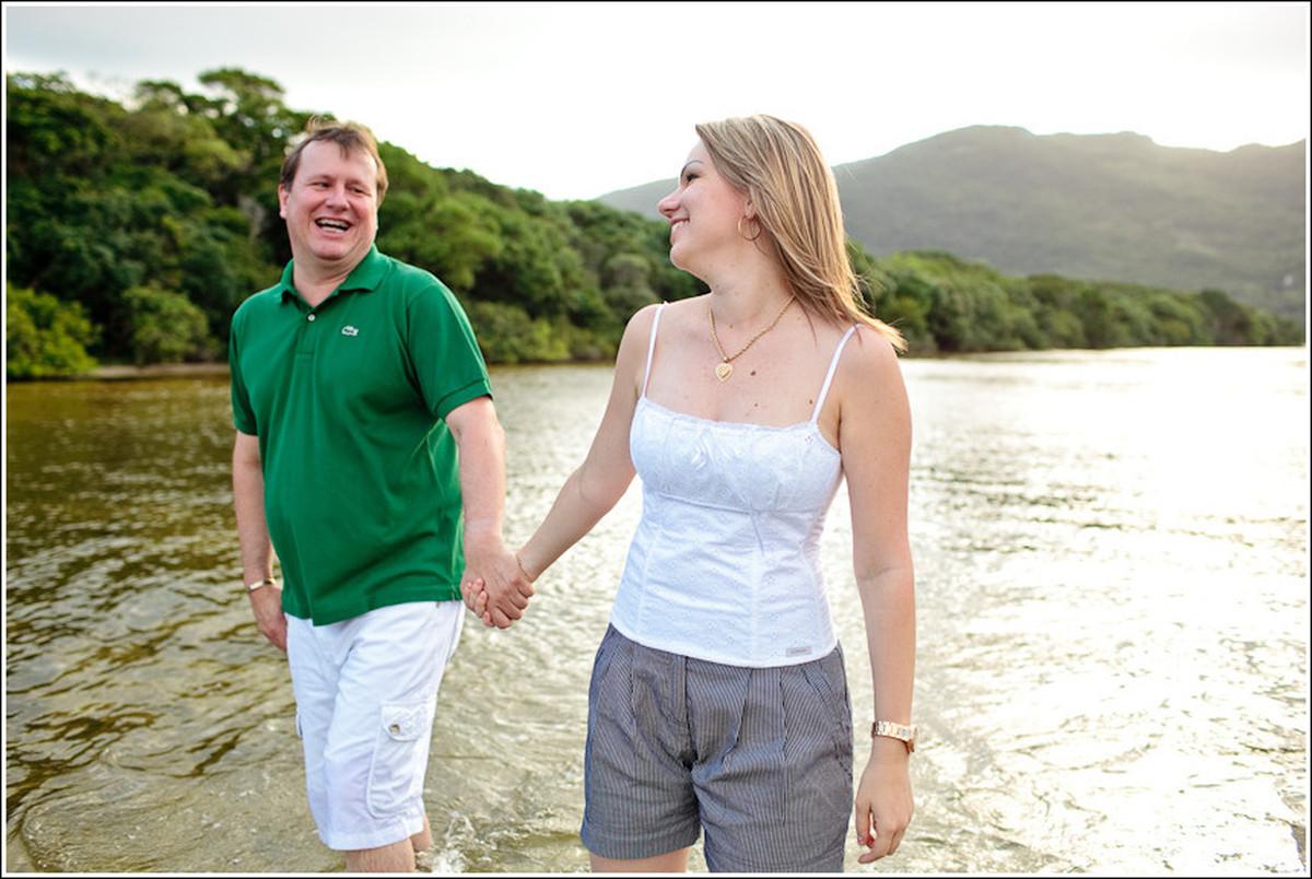 Troca de olhares do casal de namorados de mãos dadas na praia em ensaio pré-casamento