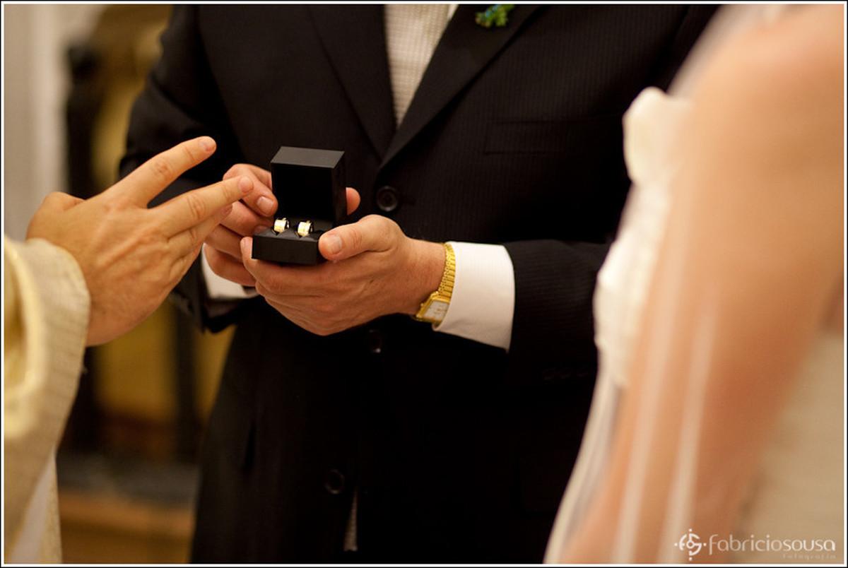 Detalhe do noivo recebendo a benção do padre nas joias alianças