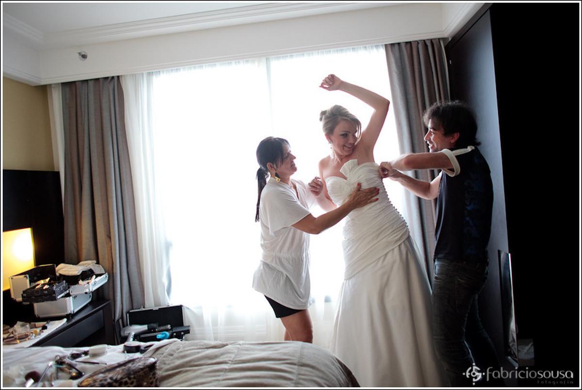 Noiva Leila recebe ajuda de 2 profissionais para vestir o vestido no quarto do hotel