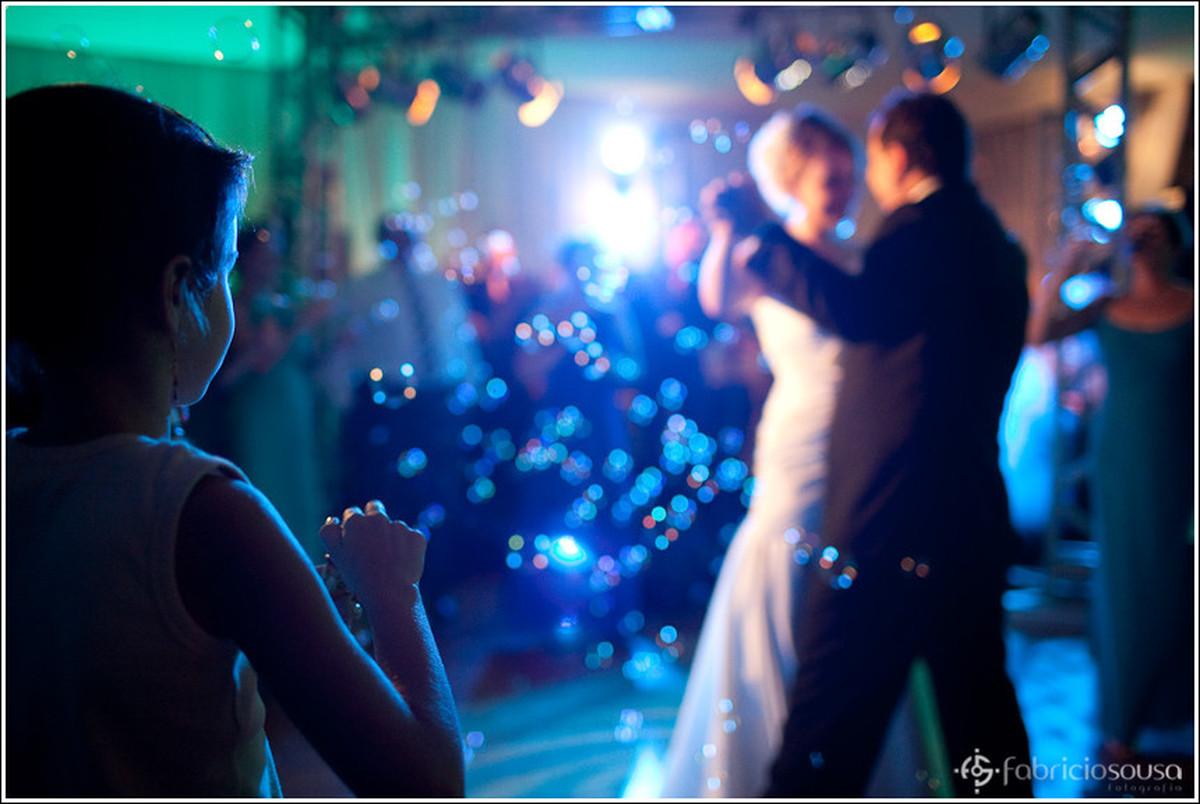 Foco em criança fazendo bolhas de sabão enquanto casal de noivos dançam a valsa na pista de dança em desfoque