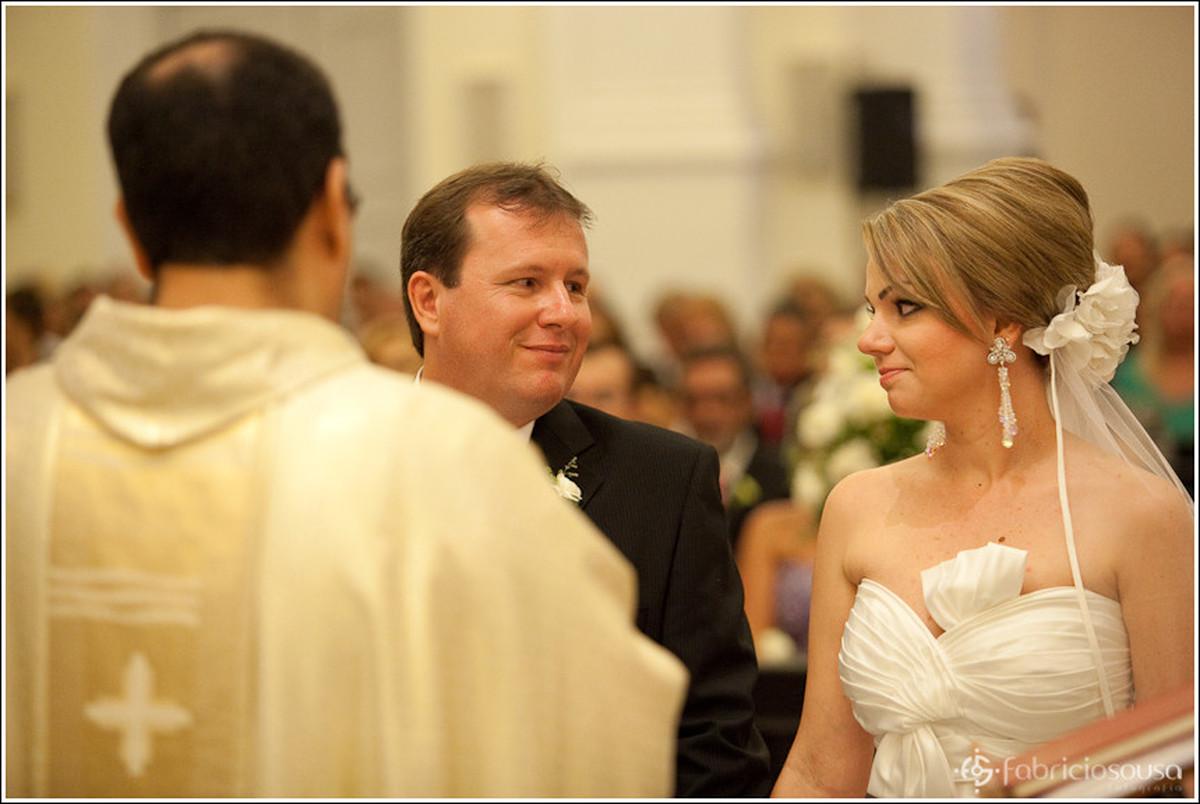 Noivo e noiva Ricardo e Leila trocam olhares no altar da igreja em frente ao padre