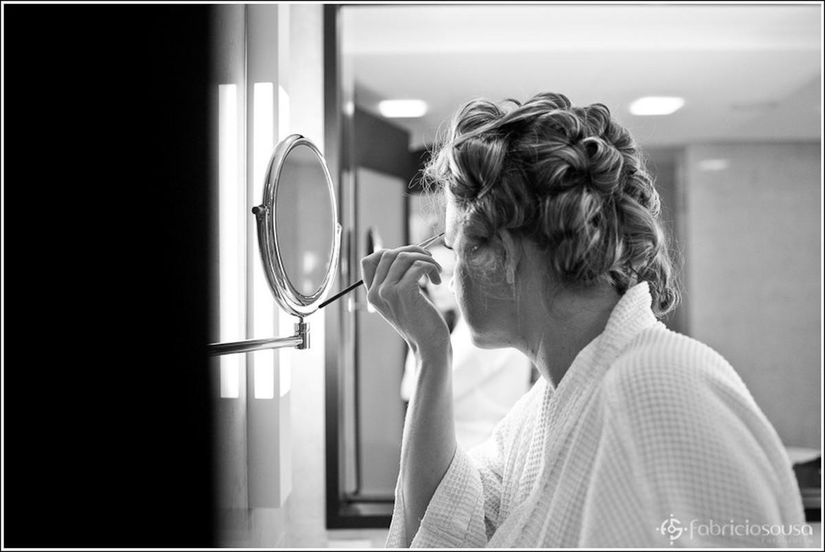 Noiva finaliza destalhes da sobrancelha se olhando no espelho preto e branco