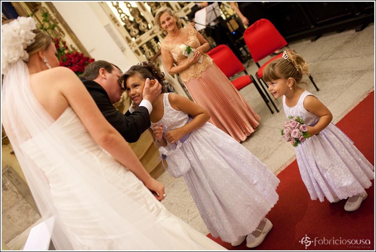 Noivo Ricardo beija uma das duas daminhas que trazem as alianças