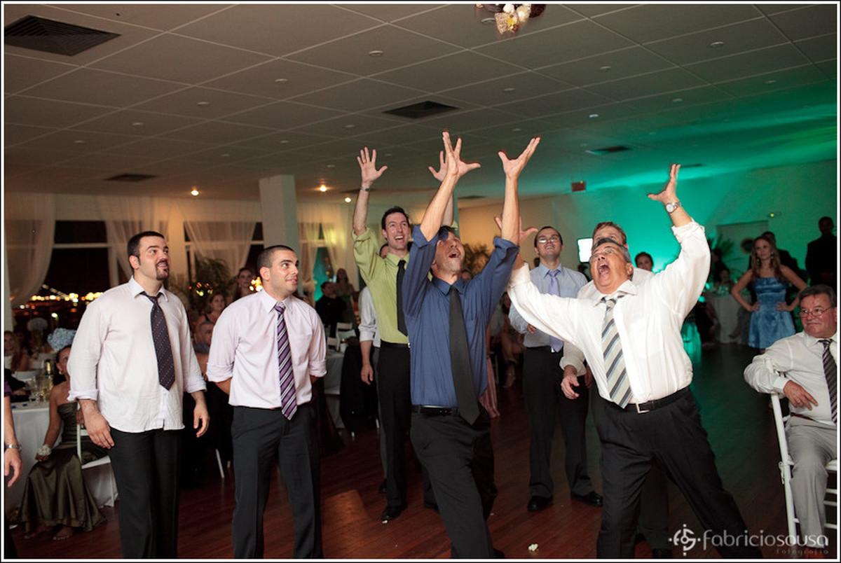 Amigos, parentes, colegas levantam os braços para tentar pegar o Santo Antonio