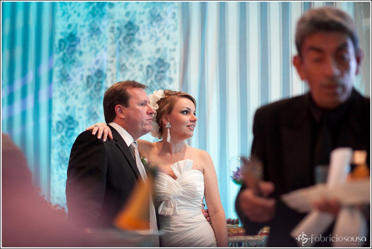 Noivo e noiva assistem atentos ao vídeo na recepção da festa no clube Veleiros