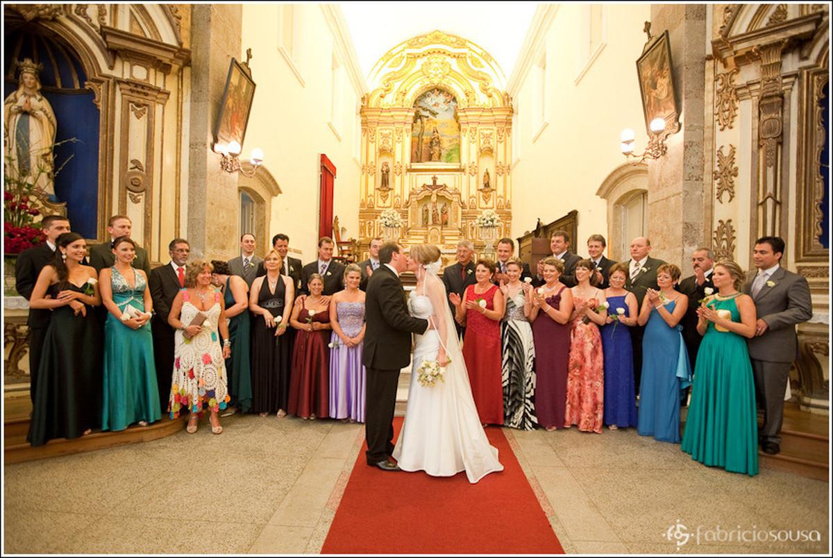Casal de noivos recém casados se beijando à frente dos padrinhos e familiares na igreja
