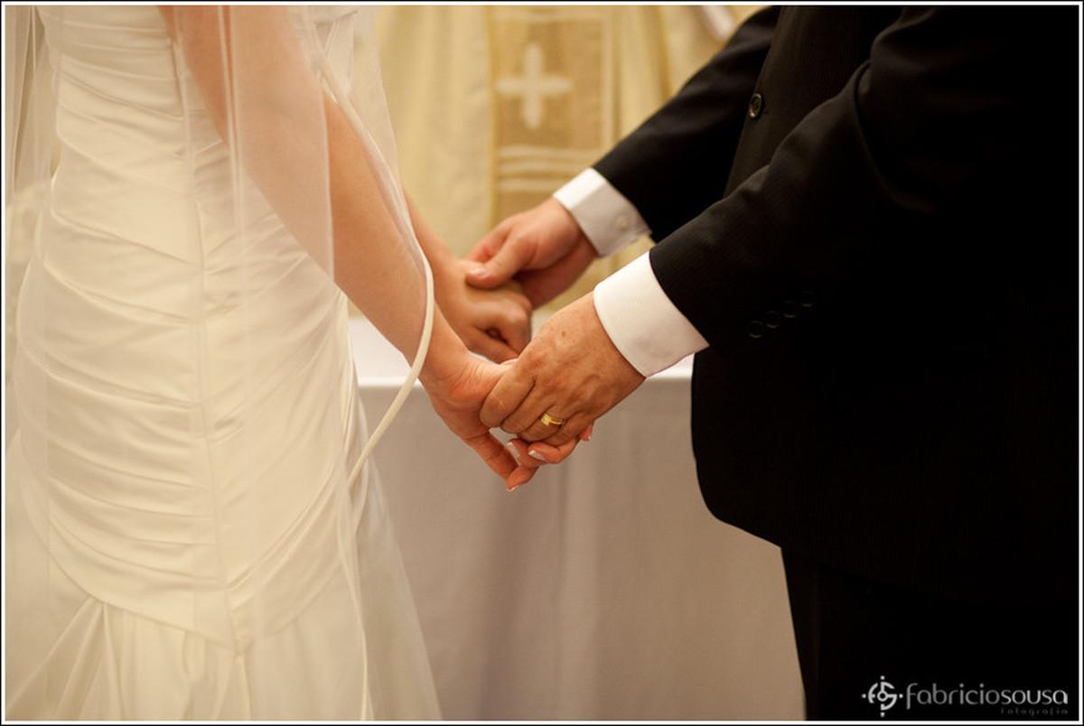 Detalhe das maos do casal de noivos no altar
