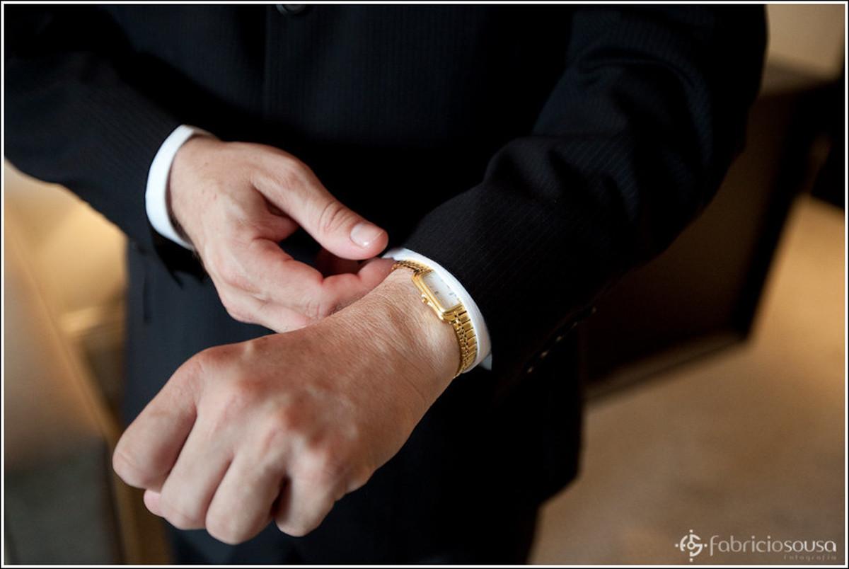 Detalhe das maos do noivo ajeitando a manga do paletó terno traje