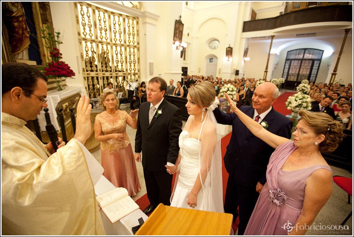 Noivos no altar recebendo benção dos presentes na igreja