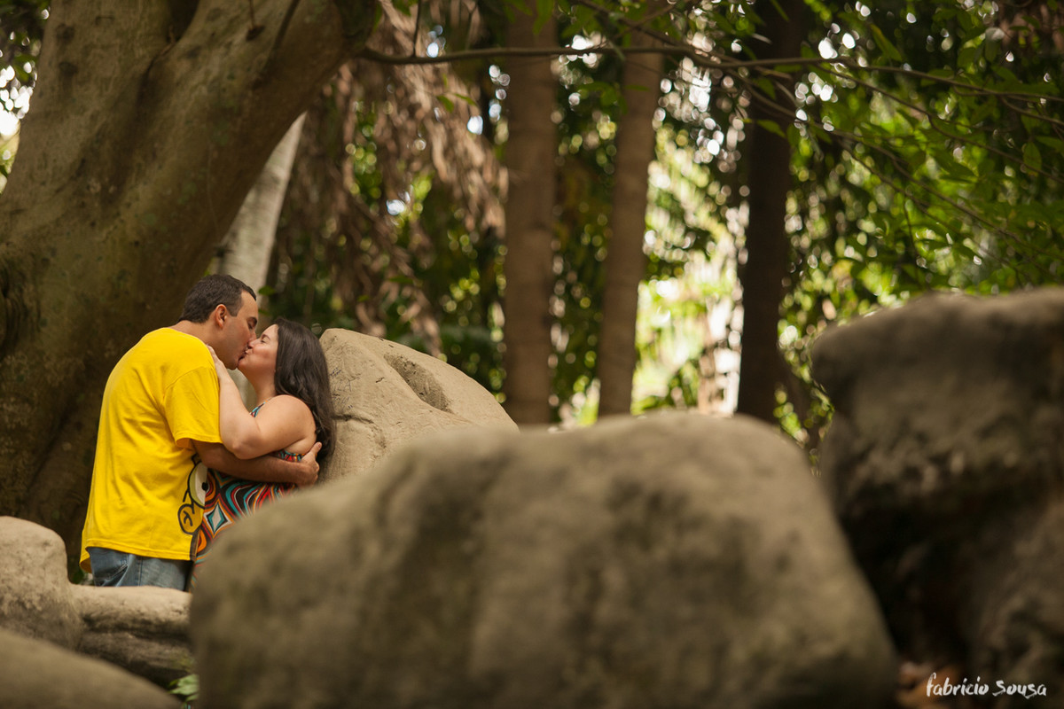 Homem e mulher abraçados encostados em um pedra entre as árvores