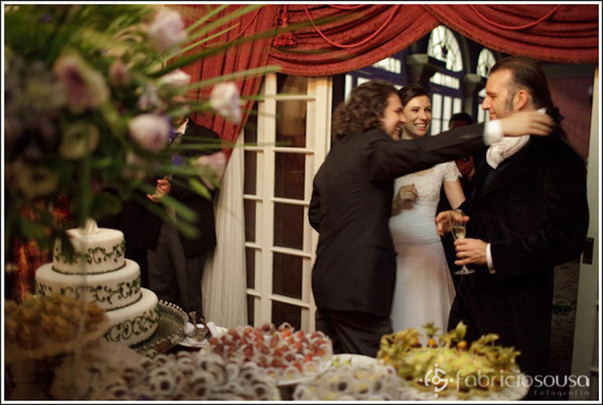 Casal de noivos recebem os cumprimentos em frente a mesa de doces