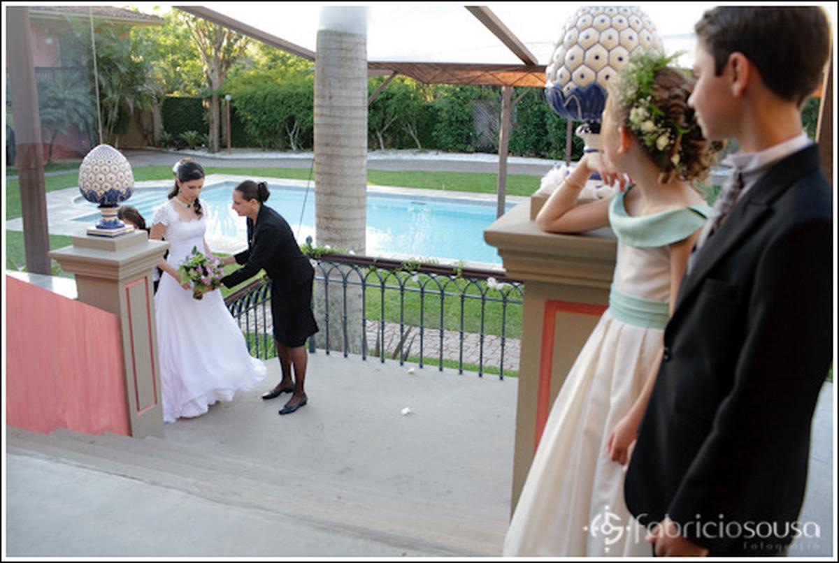 Noiva recebe buque da cerimonialista  enquanto as crianças observam atentamente