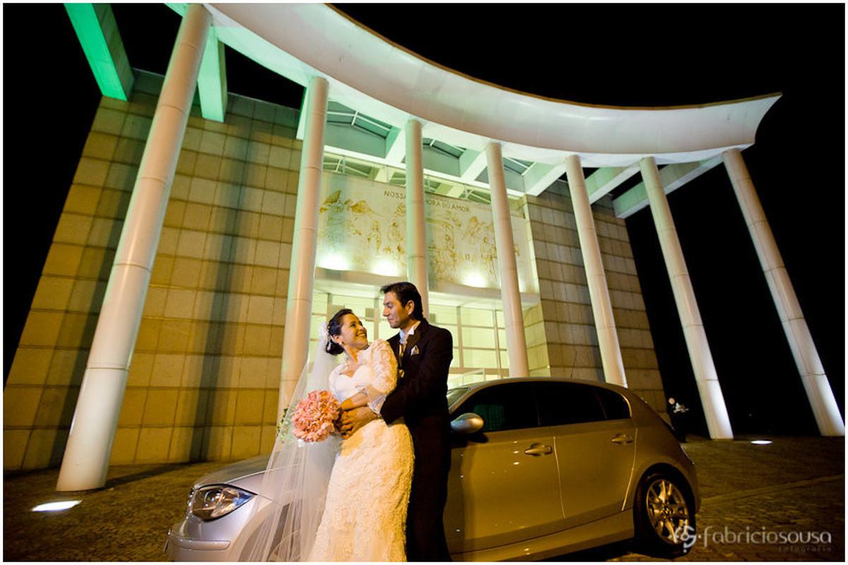 Recem casados posam junto ao carro