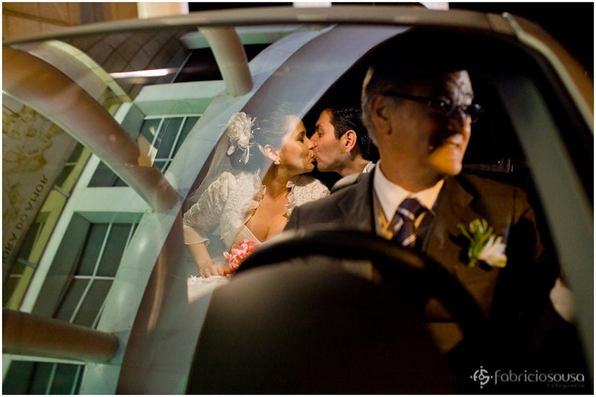 Beijo da noiva e do noivo dentro do carro
