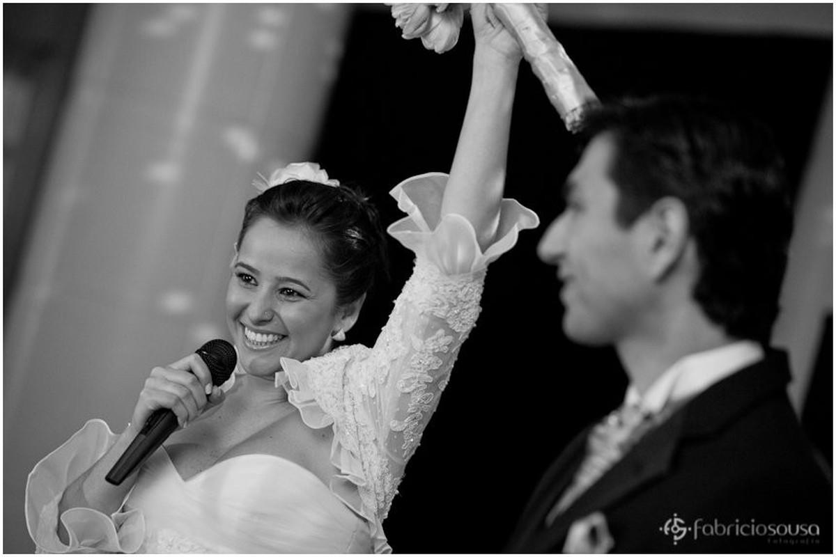 Noiva em foco no microfone e noivo desfocado ao lado
