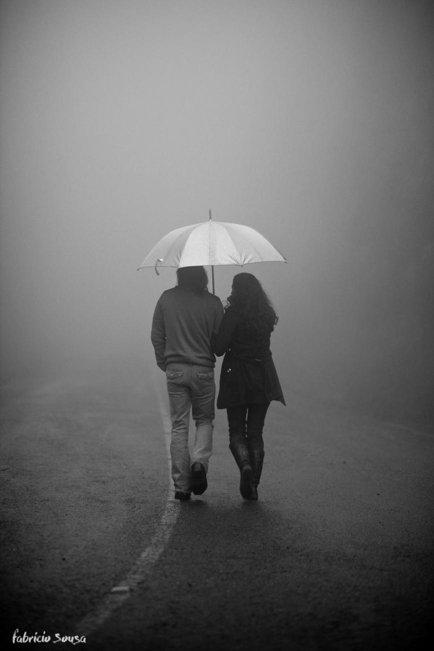Casal de costas caminhando com guarda chuva