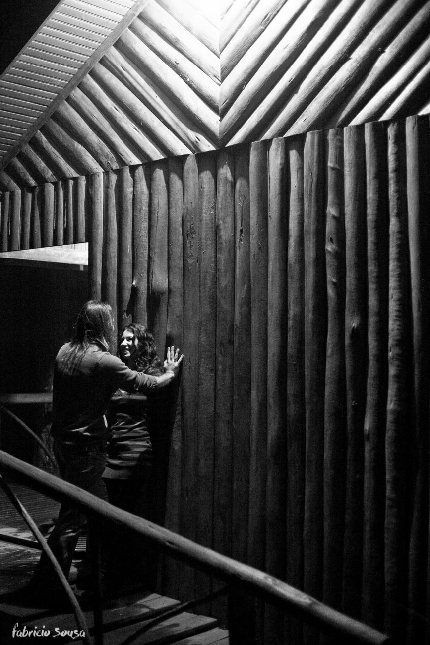 Namorados flertando encostados em parede de madeira