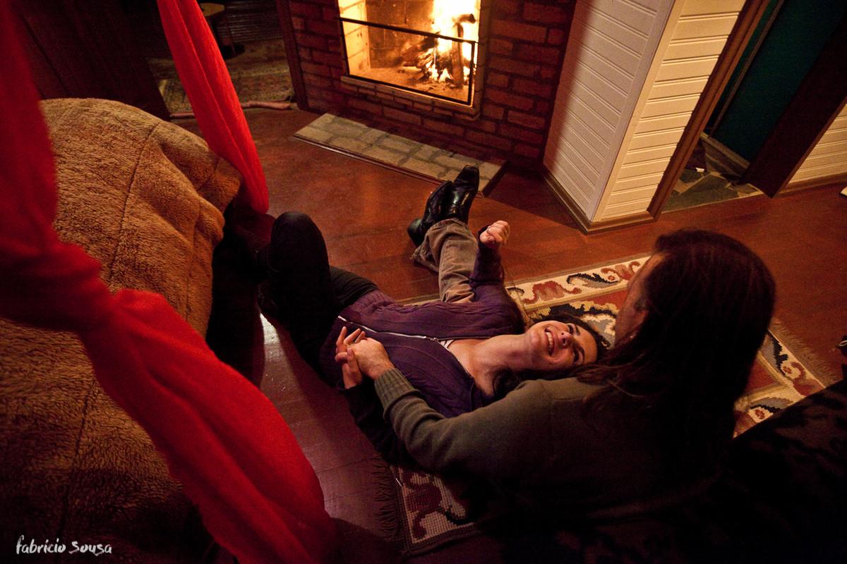Namorada deitada no colo do namorado se aquecendo em frente à lareira