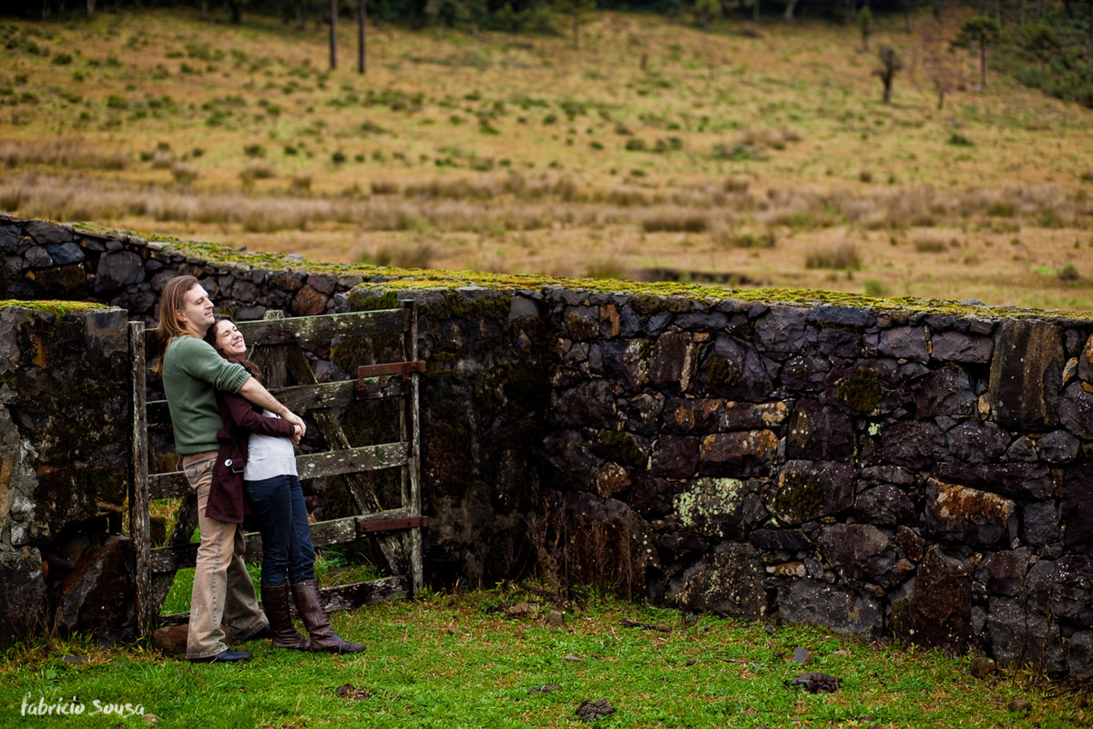 Homem e mulher apreciam a vista natural da serra em frente a uma porteira com muro de pedra em Urubici