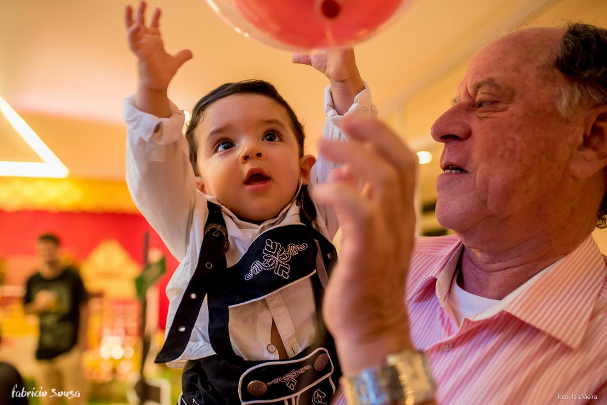 aniversariante brincando com balão no colo do vovô