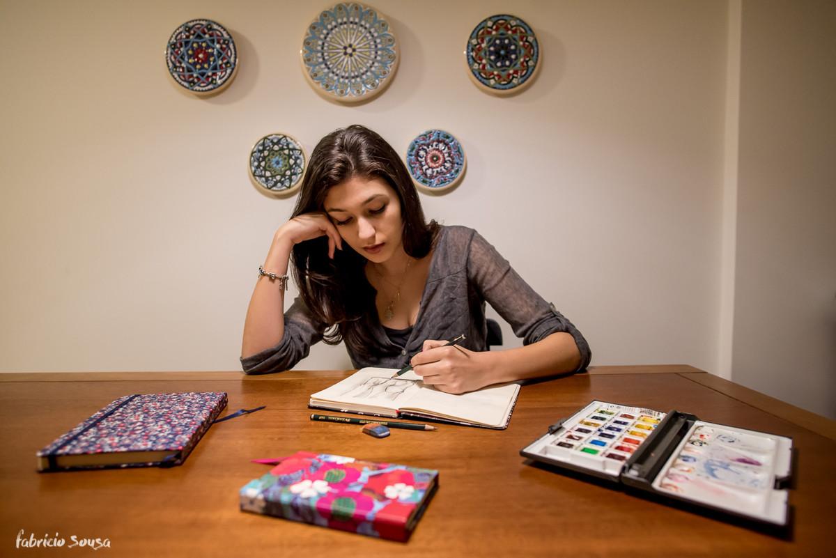 Carol desenhando no seu apartamento