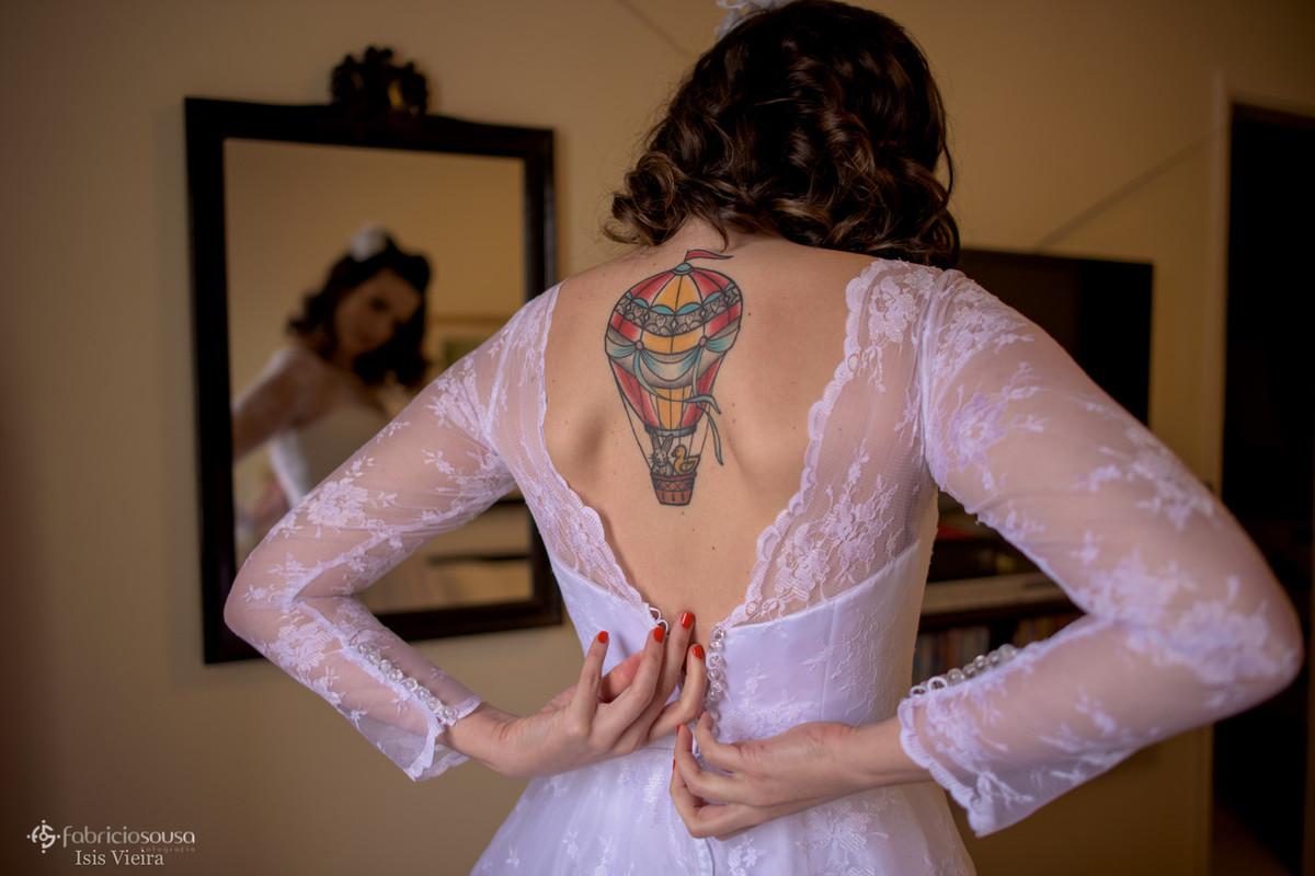a noiva abotoando o vestido boudoir