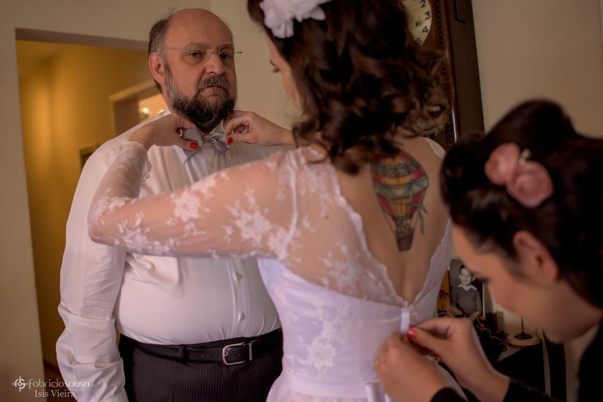 noiva arruma gravata de seu pai enquanto irmã fecha seu vestido