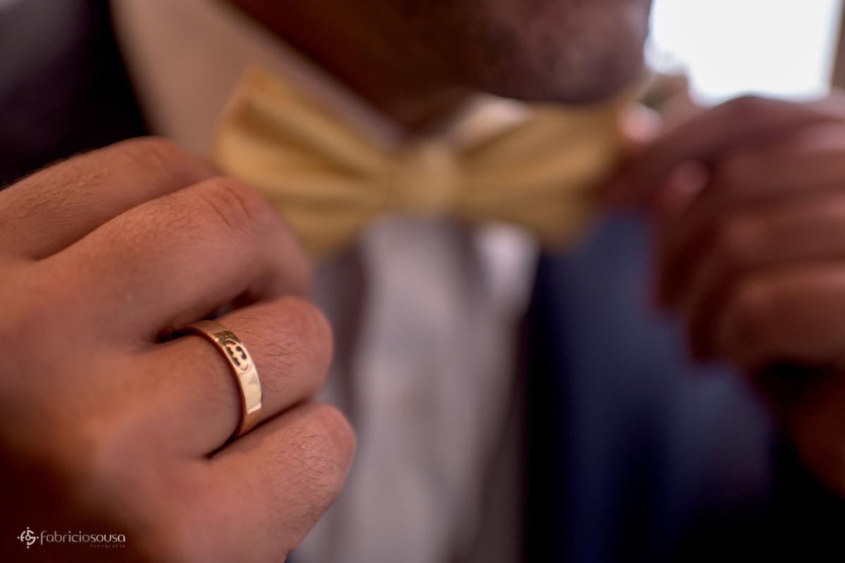 detalhe da aliança do batman e gravata borboleta amarela do noivo
