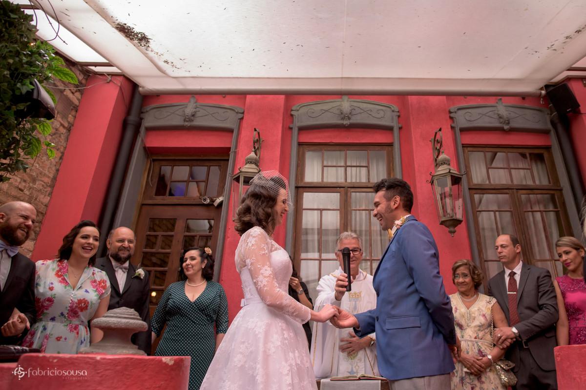 Casal de noivos atentos às palavras do padre