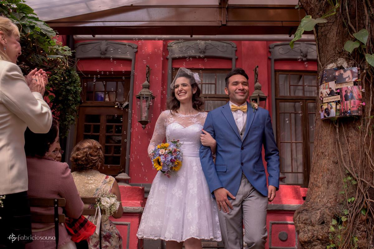 Casal de recem casados se dirigem à saída da cerimônia
