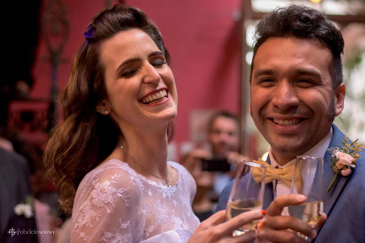 noivos sorridentes ao brindar