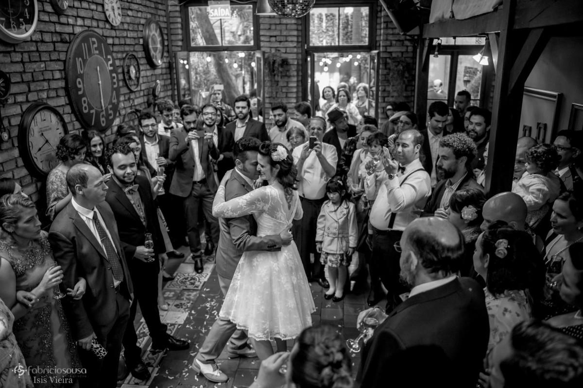 Recem casados dançam ao redor dos convidados preto e branco